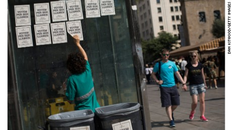 A man peels off pro-independence referendum voting posters from a wall on Friday in Barcelona.