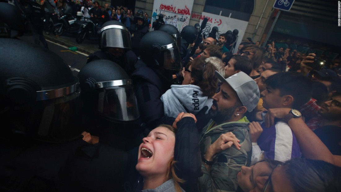 People clash with Spanish National Police outside the Ramon Llull school, designated as a polling station by the Catalan government in Barcelona, Spain, early Sunday, October 1, 2017. Catalan pro-referendum supporters vowed to ignore a police ultimatum to leave the schools they are occupying to use in a vote seeking independence from Spain.