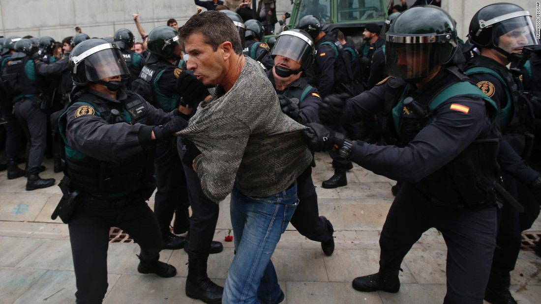 Members of Spain's national police force clear people from a polling station where Catalan President Carles Puigdemont had been expected to vote, in Sant Julia de Ramis, near Girona, Spain, Sunday, October 1, 2017. Catalan pro-referendum supporters said they would not comply with a police order to leave the schools they are occupying to use in a vote seeking independence from Spain.
