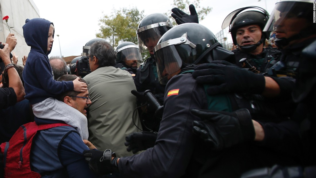 Civil guards clear people away from the entrance of a sports center, designated a polling station by the Catalan government and where Catalan President Carles Puigdemont had been expected to vote, in Sant Julia de Ramis, near Girona, Spain, Sunday, October 1, 2017.