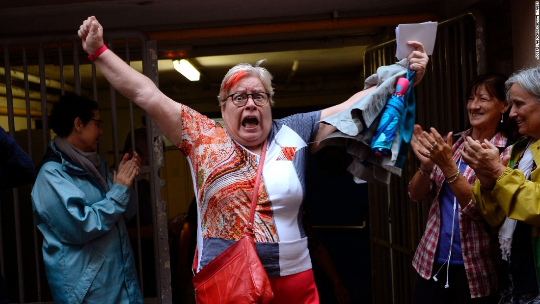 A woman celebrates outside a polling station after casting her vote in Barcelona, on October 01, 2017, in a referendum on independence for Catalonia.