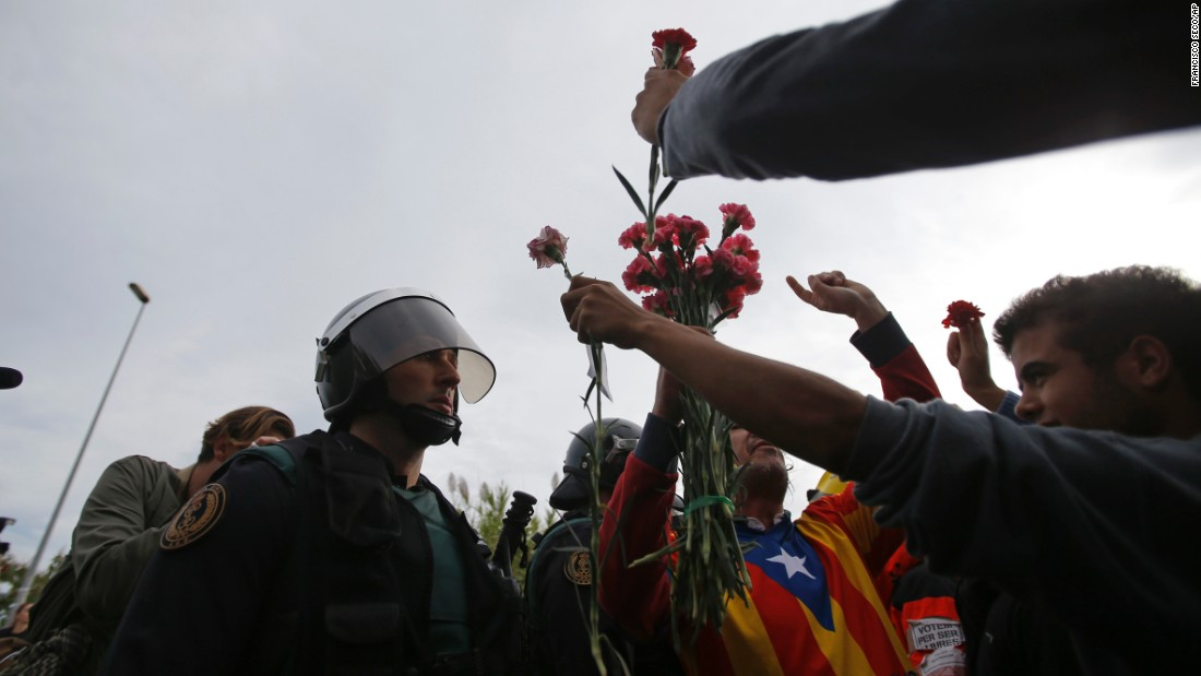People try to offer flowers to a civil guard at the entrance of a sports center, assigned to be a referendum polling station by the Catalan government in Sant Julia de Ramis, near Girona, Spain, Sunday, October 1, 2017.