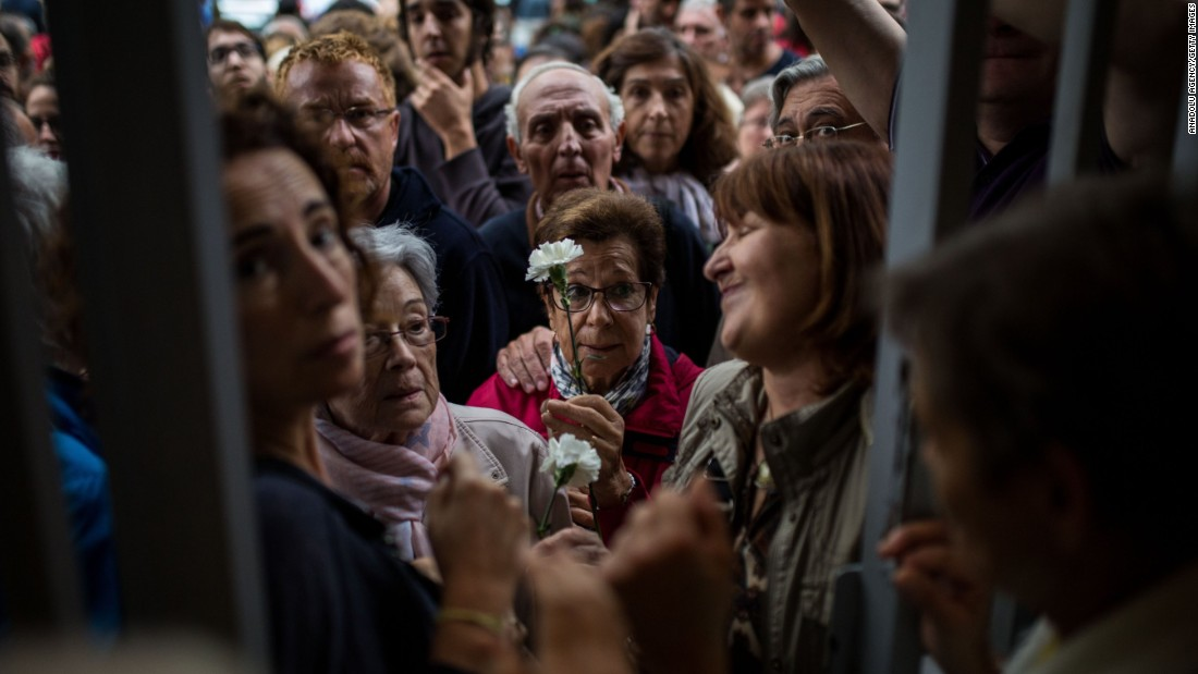 People wait at the doors of the Moises Broggi school to start voting during the Catalan independence referendum in Barcelona, Spain on Sunday, October 1, 2017.