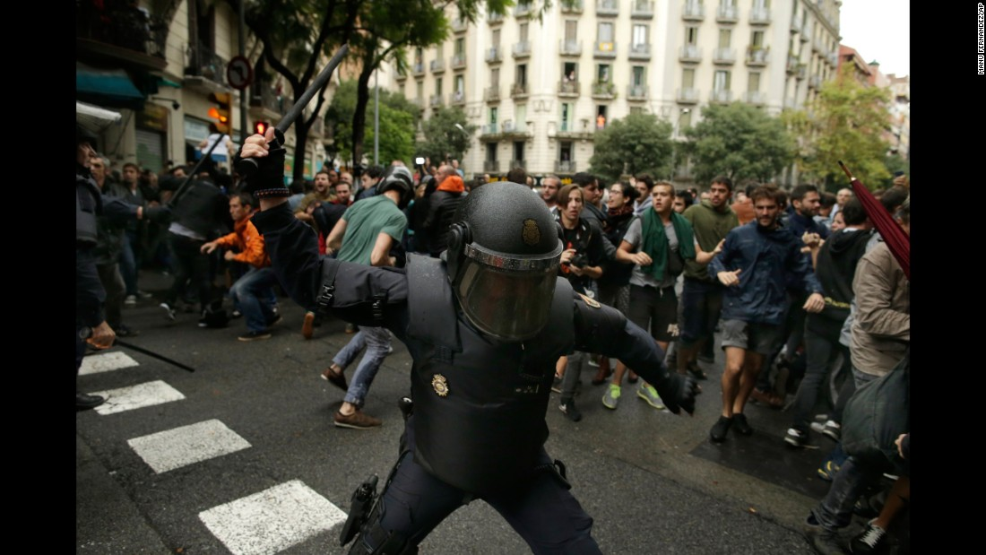 A Spanish riot police officer swings a club against would-be voters near a school assigned to be a polling station by the Catalan government in Barcelona.