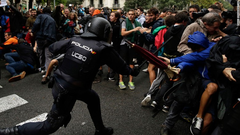 Baton-wielding Spanish National Police clash with pro-referendum supporters in Barcelona.