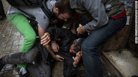 People help a man injured by a rubber bullet fired by Spanish police officers outside the Ramon Llull polling station in Barcelona.