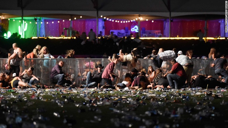 "Concertgoers dive over a fence to take cover from gunfire during the Route 91 Harvest Festival in Las Vegas on Sunday, October 1. Dozens are confirmed dead and hundreds injured in the <a href=""http://us.cnn.com/2017/10/02/us/las-vegas-shooter/index.html"" target=""_blank"">deadliest mass shooting in modern US history</a>."