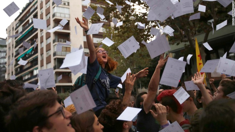 Protestors throw referendum ballots as they rally in front of Spain's ruling Partido Popular headquarters in Barcelona.