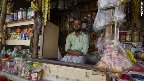 Salimullah, a Rohingya refugee who fled Myanmar in 2003, sits in front of the general store he know operates in the Kanchan Kunj Rohingya settlement in Delhi, India.