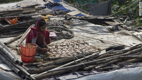 A woman in Delhi's Kanchan Kunj Rohingya settlement dries fish caught in the nearby Yamuna river.
