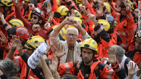 Protesters joined by firefighters raise their hands as they gather during a general strike in Barcelona Tuesday