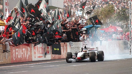 Mika Hakkinen is saluted by his McLaren team after winning the world title at Suzuka in 1998