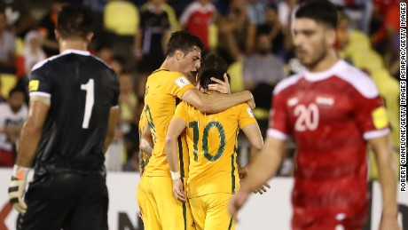 Robbie Kruse celebrates giving Australia the lead, as Syria's players look on dejected.