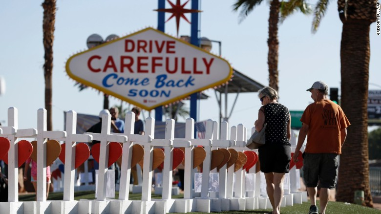 People walk by crosses placed near Las Vegas' famous sign on Thursday.