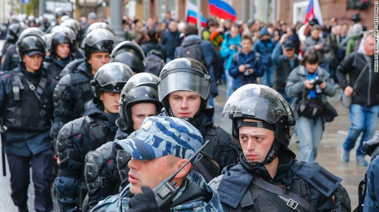 Riot police follow protesters in Moscow on Saturday.