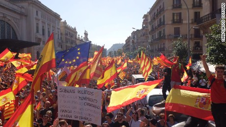 Protesters wave Spanish, Catalan and EU flags in a march for unity on Sunday in Barcelona.
