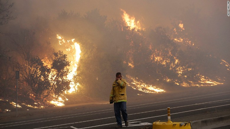 A firefighter covers his eyes as he walks past a burning hillside in Santa Rosa, California, on Monday, October 9. Wildfires whipped by powerful winds swept through Northern California, sending residents on a flight to safety through smoke and flames as homes burned.