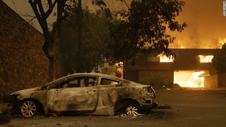 The remains of a car sit near the Fountaingrove Inn Hotel on Monday as the Santa Rosa hotel burns in the background.