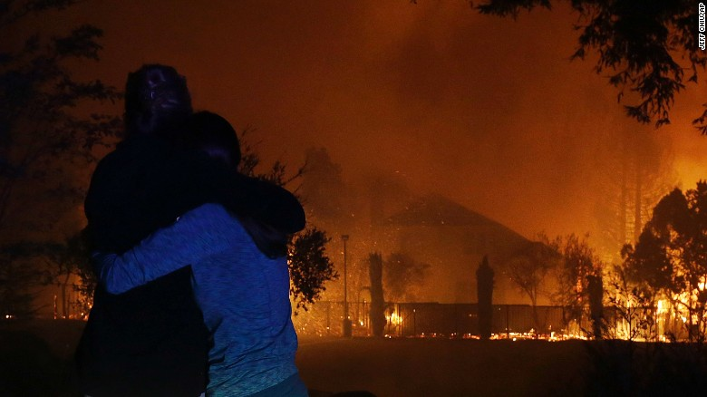 Two women hug as they watch houses burn Monday in Santa Rosa.