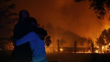 Two women hug as they watch houses burn in Santa Rosa on October 9.