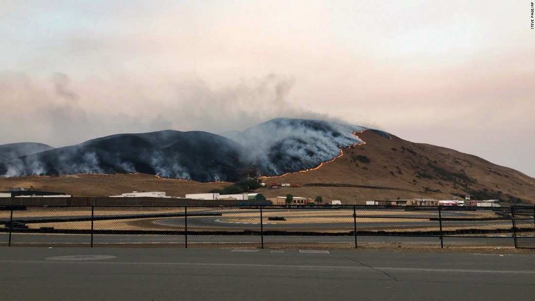 A wildfire burns behind the Sonoma Raceway on October 9.