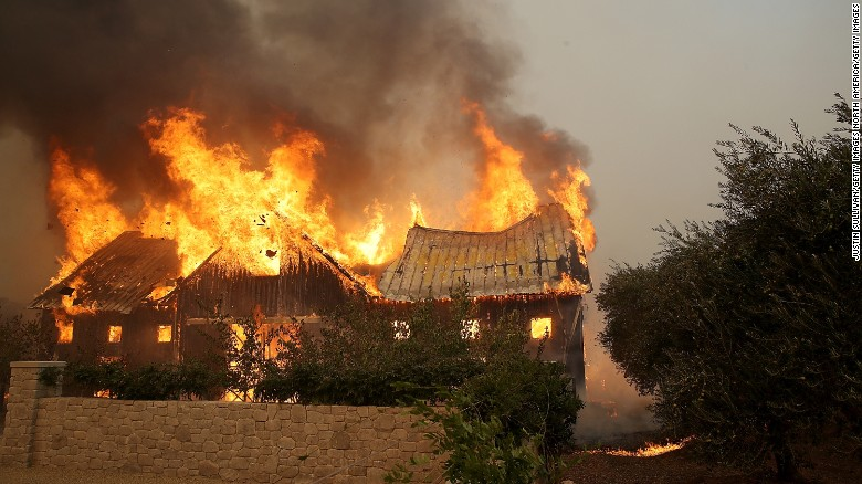 Fire consumes a barn Monday as wildfire moves through the area in Glen Ellen, California. Tens of thousands of acres and dozens of homes and businesses have burned in Napa and Sonoma counties.