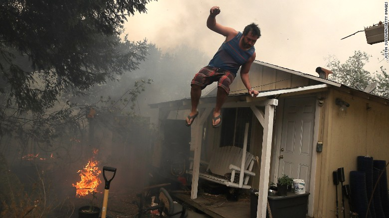 A resident rushes to save his home on Monday in Glen Ellen.