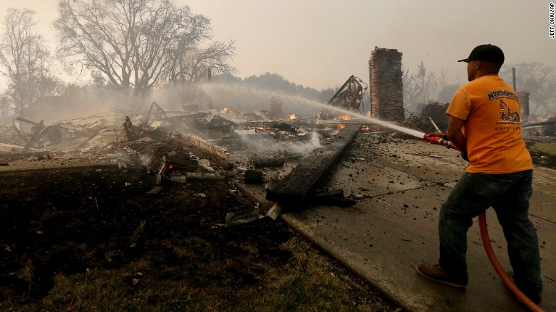 A man hoses down hot spots on Monday where a house burned down in Santa Rosa.