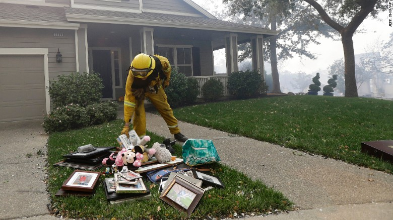 A firefighter on Monday places belongings onto the lawn of a home in Santa Rosa on Monday.