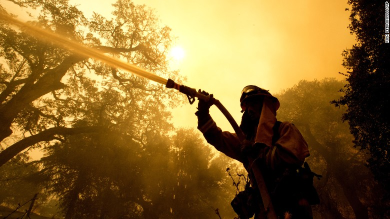 Napa County firefighter Jason Sheumann sprays water Monday on a home as he battles flames from a wildfire.