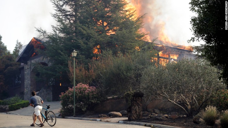 A man walks Monday next to a burning house in the Silverado Crest subdivision in Napa.
