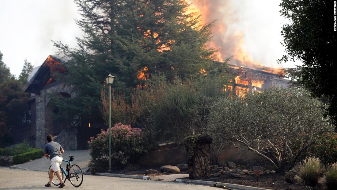 A man passes a burning house in Napa on October 9.
