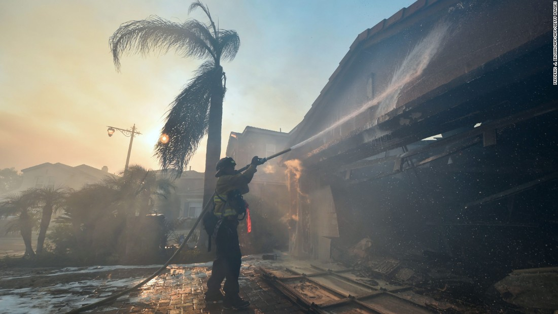 A firefighter douses flames at a home in Anaheim on October 9.