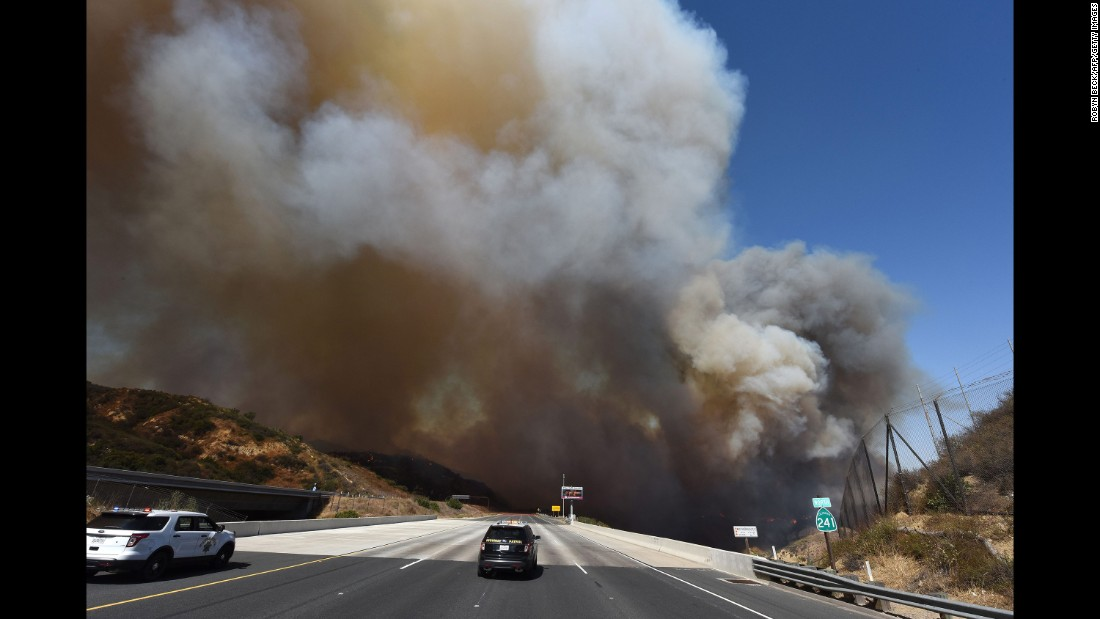 Police cars block State Route 241 as smoke rises above Orange on October 9.