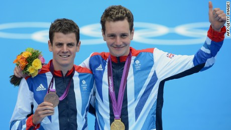Alastair Brownlee (R) and brother Jonny pose with their medals after the men's triathlon