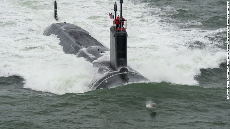 """A dolphin swims in front of the Virginia-class attack submarine USS John Warner during its sea trials in May 2015. Virginia-class subs, displacing 7,800 tons and at 377 feet long, """"are designed to seek and destroy enemy submarines and surface ships; project power ashore with Tomahawk cruise missiles and special operation forces (SOF); carry out inntelligence, surveillance, and reconnaissance (ISR) missions; support battle group operations; and engage in mine warfare,"""" according to the Navy."""