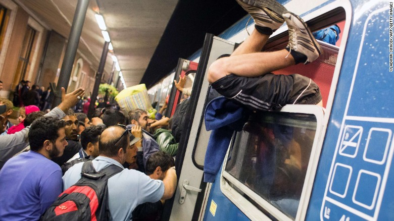 A man climbs through a window as migrants struggle to get on a train in Hungary in September 2015.