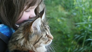 Portrait of a 6-year-old artist with autism and her therapy cat