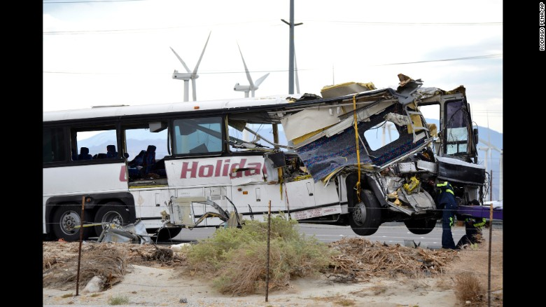 Workers prepare to haul away the mangled tour bus.