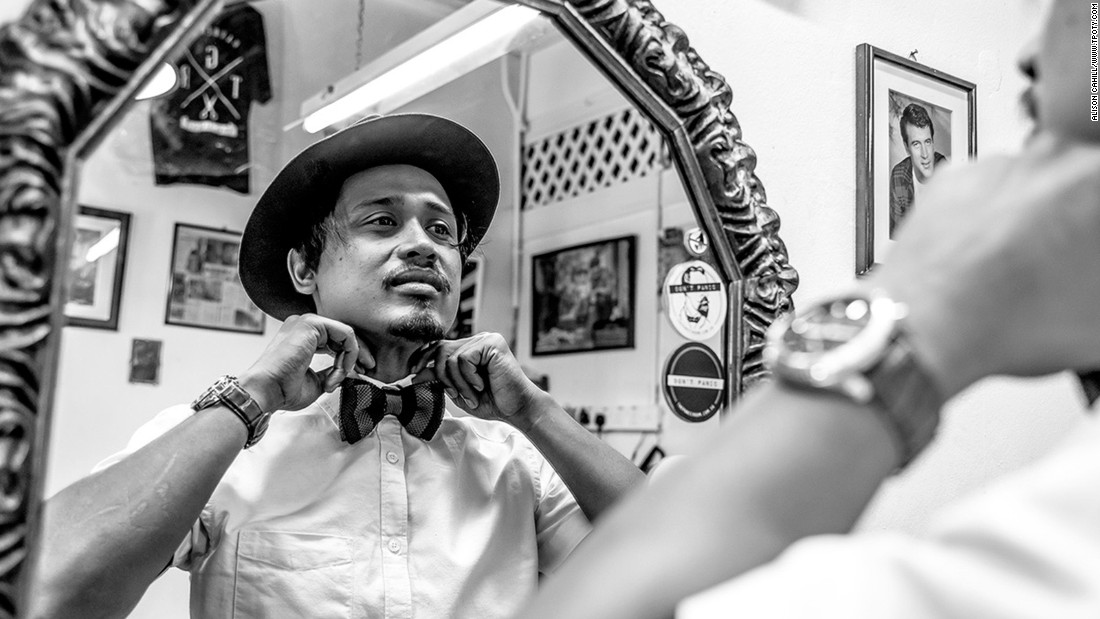 Elyas, the head barber and owner of Son & Dad Barbers in George Town, Penang, Malaysia, straightens his collar in this image by UK photographer, Alison Cahill, the winner of the New Talent -- Eye to Eye category.
