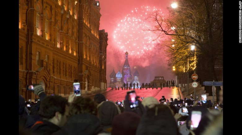 People watch as fireworks explode over the Kremlin in Moscow, Russia.