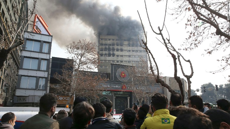 People watch as smoke rises from the windows of the Plasco building.