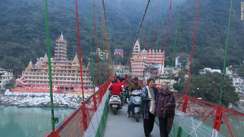Pedestrians and motorists share a narrow path on Lakshman Jhula.
