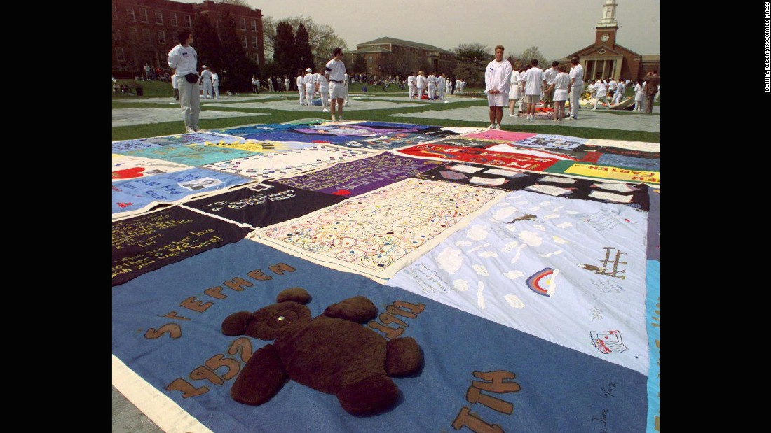 A teddy bear adorns one more than 400 panels of the AIDS Memorial Quilt as volunteers stand by silently during a 1996 ceremony at <strong>Elmhurst College</strong> in Elmhurst, Ilinois.
