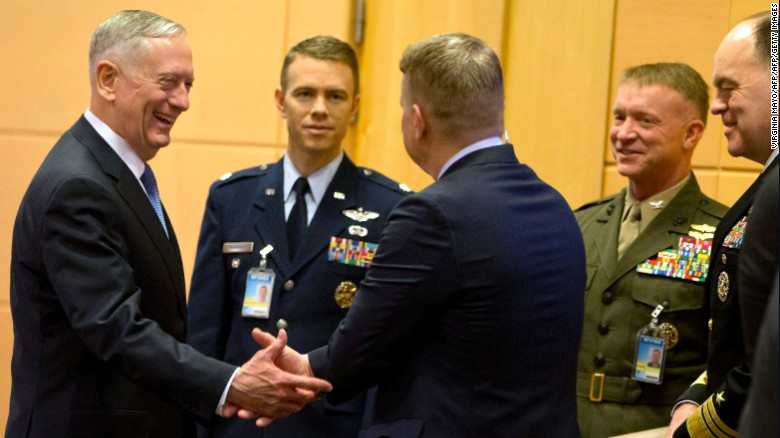 James Mattis (L) speaks with members of his delegation prior to a meeting at NATO headquarters in Brussels.
