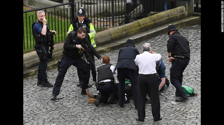 "A police officer points a gun at a man on the ground outside Parliament. ""We are treating this as a terrorist incident until we know otherwise,"" said London's Metropolitan Police."