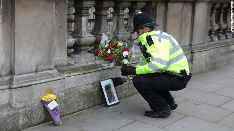A police officer lays a floral tribute from a member of the public beside a photo of Keith Palmer, the Metropolitan Police constable who was stabbed to death near the Houses of Parliament in London during a terror attack on March 23, 2017.