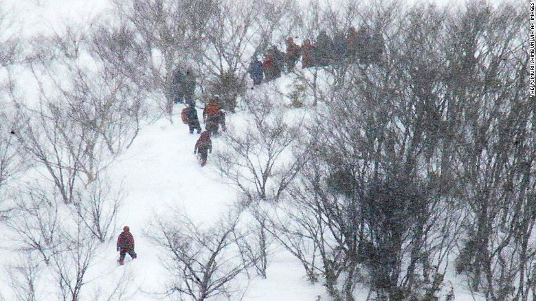 Rescue team members climb the mountain at Nasu Onsen Family Ski Resort.