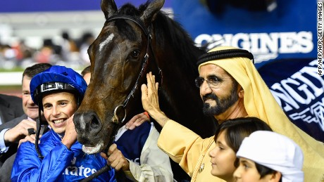 UAE Prime Minister and Ruler of Dubai Sheikh Mohammed bin Rashid al-Maktoum (C-R) celebrates with Jockey William Buick (C-L) and horse Jach Hobbs (C) after they won the Longines Dubai Sheema Classic at the Dubai World Cup in the Meydan Racecourse on March 25, 2017 in Dubai. / AFP PHOTO / Abdulqader  AL-ANI        (Photo credit should read ABDULQADER  AL-ANI/AFP/Getty Images)