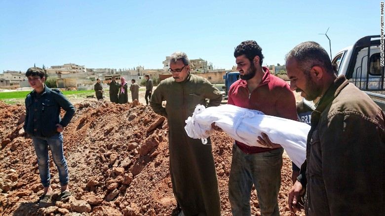 Syrians bury the bodies of victims of the attack in Khan Sheikhoun, in Idlib province, on April 5, 2017.